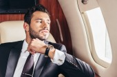 handsome businessman in suit looking through window in private plane