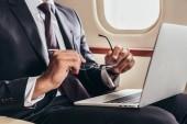 oříznutý pohled na obchodníka v obleku s notebookem a brýlemi v soukromém letadle