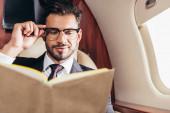 selektivní zaměření pohledný podnikatel v obleku čtení knihy v soukromém letadle
