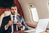 handsome businessman in suit holding cup of coffee in private plane