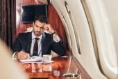 schöner Geschäftsmann im Anzug schreibt im Privatflugzeug in Notizbuch