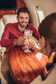 Lächelnder Freund und Freundin klirren mit Champagnergläsern im Privatflugzeug