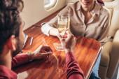 Freund und Freundin klirren mit Champagnergläsern im Privatflugzeug