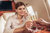 Freund und lächelnde Freundin klirren mit Champagnergläsern im Privatflugzeug