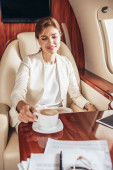smiling businesswoman in suit taking cup of coffee in private plane