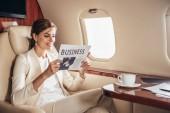 usmívající se podnikatelka v obleku čtení noviny podnikání v soukromém letadle