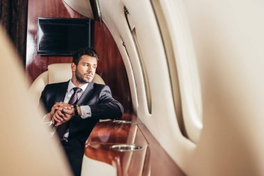 Selective focus of handsome businessman in suit looking through window in private plane stock vector
