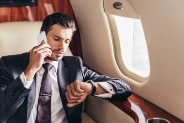 Handsome businessman in suit talking on smartphone and looking at wristwatch in private plane stock vector