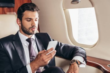 Handsome businessman in suit using smartphone in private plane stock vector