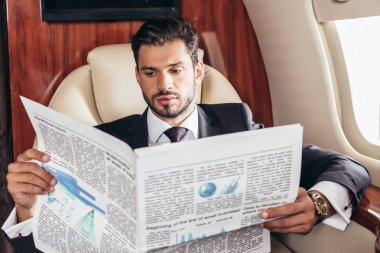 Handsome businessman in suit reading newspaper in private plane stock vector