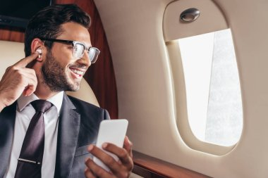 Smiling businessman listening music and using smartphone in private plane stock vector