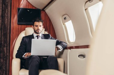 Selective focus of handsome businessman in suit using laptop in private plane stock vector