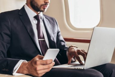 Cropped view of businessman in suit using laptop and smartphone in private plane stock vector