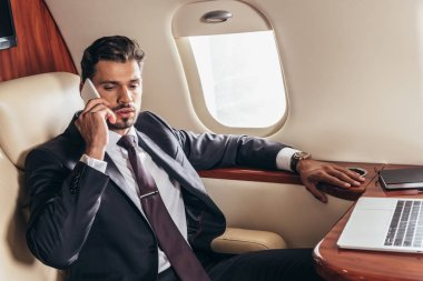 Handsome businessman in suit talking on smartphone in private plane stock vector