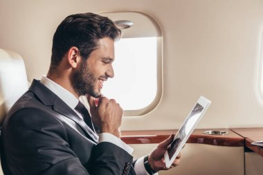 Handsome businessman in suit using digital tablet in private plane stock vector