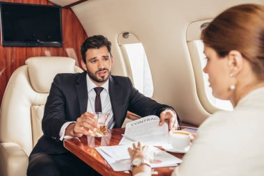 Businessman with glass showing contract to businesswoman in private plane stock vector