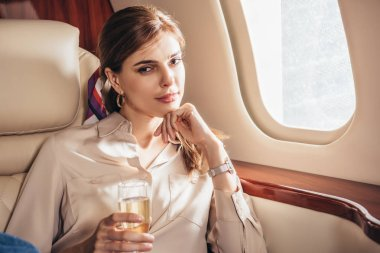 Attractive woman in shirt holding champagne glass in private plane stock vector