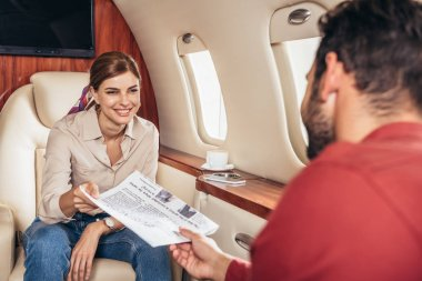 Selective focus of boyfriend giving newspaper to girlfriend in private plane stock vector