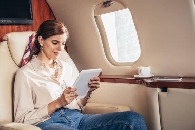 Attractive woman in shirt using digital tablet in private plane stock vector