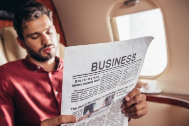 Handsome man in shirt reading business newspaper in private plane stock vector
