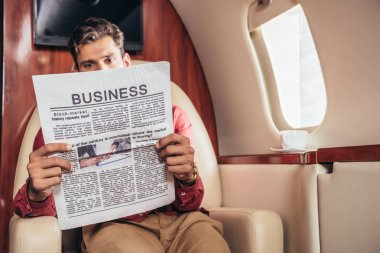 Handsome man reading business newspaper in private plane stock vector
