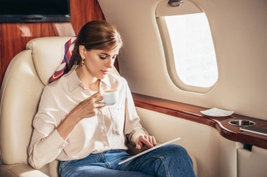 Attractive woman in shirt using digital tablet and holding cup of coffee in private plane stock vector