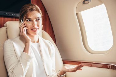 Attractive businesswoman in suit talking on smartphone in private plane stock vector