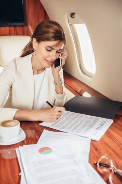 Attractive businesswoman in suit signing contract in private plane stock vector
