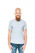 usmívající se pohledný vousatý muž v šedém tričku, izolovaný na bílém