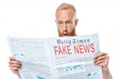 překvapený vousatý muž čte noviny s falešnými zprávami, izolovaný na bílém