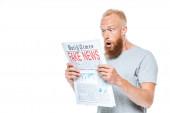 šokovaný vousatý muž čte noviny s falešnými zprávami, izolovaný na bílém