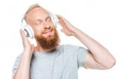 šťastný muž se zavřenýma očima poslouchající hudbu se sluchátky, izolovaný na bílém