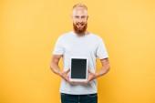 veselý muž ukazující digitální tablet s prázdnou obrazovkou, izolovaný na žluté