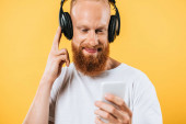 Photo smiling beard man listening music with headphones and smartphone, isolated on yellow