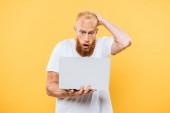 aggódó szakállas férfi használ laptop, elszigetelt sárga