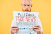 selektivní zaměření seriózní muž čtení novin s falešnými zprávami, izolované na žluté