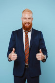 smiling bearded businessman in suit showing thumbs up, isolated on blue