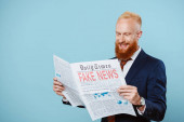 veselý vousatý obchodník, který čte noviny s falešnými zprávami, izolovaný na modré