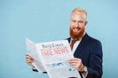 usmívající se vousatý obchodník, který čte noviny s falešnými zprávami, izolovaný na modré