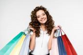 krásná usměvavá dívka drží nákupní tašky, izolované na bílém
