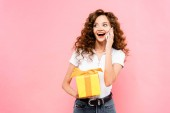 izgatott göndör lány gazdaság ajándék doboz és beszél okostelefon, elszigetelt rózsaszín