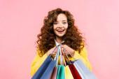 gyönyörű göndör lány gazdaság bevásárló táskák, elszigetelt rózsaszín