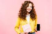 attraktive lockige Mädchen zeigt Geschenk und Smartphone mit leerem Bildschirm, isoliert auf rosa