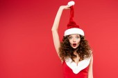atraktivní překvapená dívka pózující v kostýmu Santa Clause a klobouku, izolovaná na červené