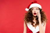 attraktive schockierte Frau im Weihnachtsmannkostüm, die auf dem Smartphone spricht, isoliert auf Rot