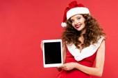 gyönyörű lány télapó jelmezben mutatja digitális tabletta üres képernyőn, elszigetelt piros