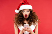 shocked woman in santa costume using smartphone, isolated on red