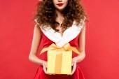 ostříhaný pohled na dívku v kostýmu Santa držící vánoční dárek, izolované na červené