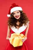 mosolygós göndör lány télapó jelmezben tartja karácsonyi ajándék, elszigetelt piros