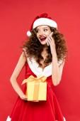 boldog lány télapó jelmez gazdaság karácsonyi ajándék és beszél okostelefon, elszigetelt piros